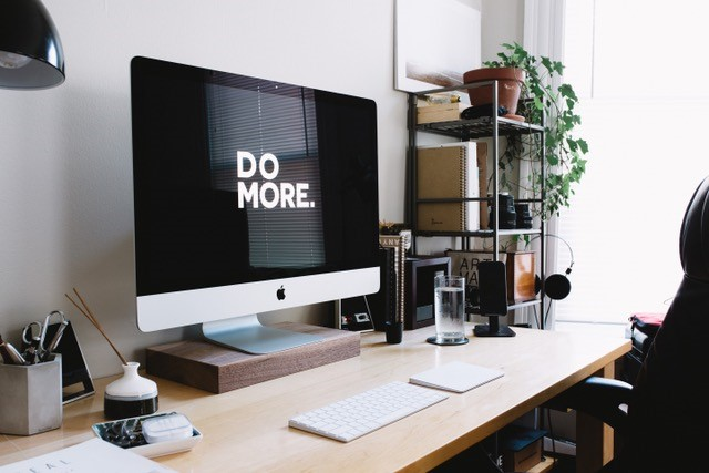 Computer on desk with Do More on the monitor